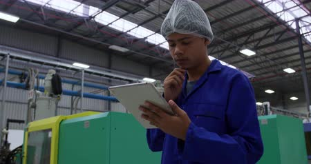 macacão : Low angle side view of focused mixed race male worker working in a busy factory warehouse, wearing a hair net and overalls, using a tablet computer Vídeos