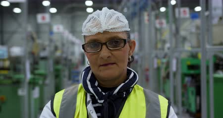 engradado : Portrait of focused mixed race female worker standing and looking to camera in a busy factory warehouse, wearing hair net and smiling