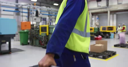 жилет : Side view of focused mixed race male worker working in a busy factory warehouse, wearing a hair net, overalls and a high visibility vest, pulling a trolley with materials through the factory factory Стоковые видеозаписи