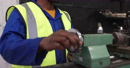 vest : Side view of focused mixed race male worker working in a busy factory warehouse, wearing hair net and safety glasses, preparing and checking metal parts in a factoru machine shop Stock Footage