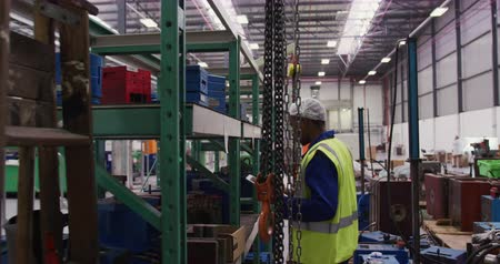 vest : Side view of focused mixed race male worker working in a busy factory warehouse, wearing hair net, overalls and a high visibility vest, using a digital tablet and checking metal parts on storage shelves Stock Footage