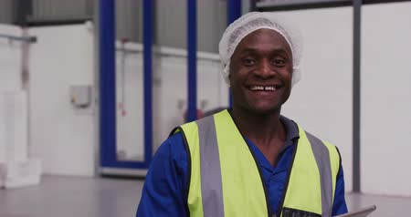munkás : Portrait of a happy African American male worker working in a busy factory warehouse, wearing a hair net, overalls and a high visibility vest, smiling and looking to camera