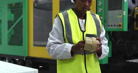 visibilidad : Front view of focused African American female worker working in a busy factory warehouse, wearing a hair net, overalls and a high visibility vest, preparing and checking plastic parts