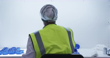 visibilidad : Rear view close up of focused mixed race female worker working in a busy factory warehouse, wearing hair net and high visibility vest, preparing and checking plastic parts