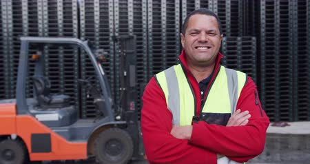 magazyn : Portrait of a confident mixed race male worker working outside a factory warehouse, standing beside a forklift truck, wearing high visibility vest, smiling and looking to camera, with arms crossed, in slow motion