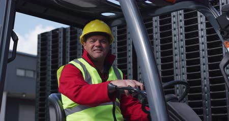 vest : Portrait close up of a confident mixed race male worker working at a busy factory warehouse, wearing high visibility vest and protective helmet, driving a forklift truck outside, smiling and looking to camera, in slow motion