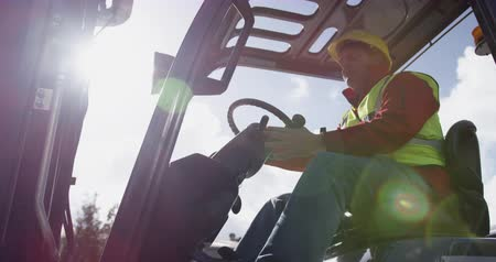 vorkheftruck : Low angle side view of focused mixed race male worker working at a busy factory warehouse, wearing high visibility vest and protective helmet, driving a forklift truck outside, backlit by sunlight, in slow motion