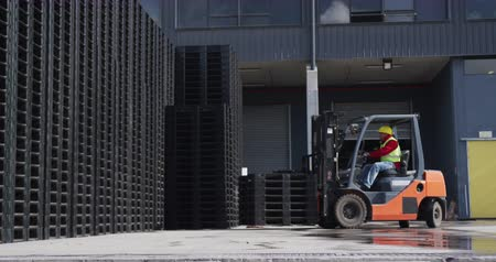 vorkheftruck : Side view of a confident mixed race male worker working at a busy factory warehouse, wearing high visibility vest and protective helmet, driving a forklift truck outside and lifting crates
