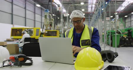 repartidor : Front view of focused mixed race male worker working in a busy factory warehouse, wearing a hair net and high visibility vest, sitting and using laptop computer