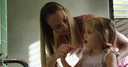 učit : Front view close up of a Caucasian woman enjoying free time at home in the bathroom, helping brushing her young daughter teeth with a toothbrush in slow motion.