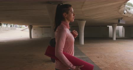 provést : Side view of a Caucasian woman in sportswear, on her way to fitness training on a cloudy day, walking under a bridge carrying a sports bag and a yoga mat, slow motion