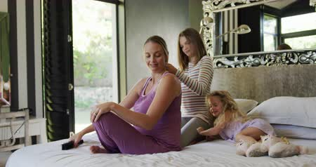 escovação : Side view of a teenage Caucasian girl enjoying free time at home in the bedroom, brushing her pregnant mother hair while a younger daughter is lying on bed and having fun in slow motion. Vídeos