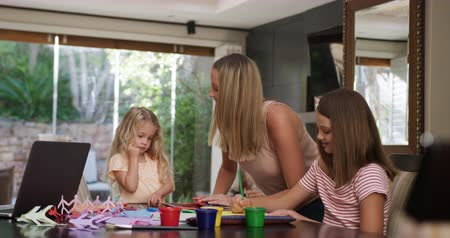výřez : Front view of a Caucasian woman enjoying free time at home in the dining room helping her teenage and younger daughter painting pictures in slow motion. Dostupné videozáznamy