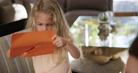 jídelna : Front view of a young Caucasian girl enjoying free time at home in the dining room, making cutouts from an orange piece of paper, using scissors in slow motion. Dostupné videozáznamy