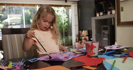 výřez : Front view of a young Caucasian girl enjoying free time at home in the dining room, painting a picture on a violet piece of paper in slow motion.