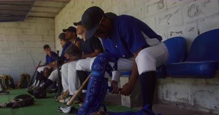 beisebol : Side view of a mixed race male baseball player preparing to play in the catcher position before a game, sitting in a changing room, putting on leg pads, with his teammates talking in the background in slow motion