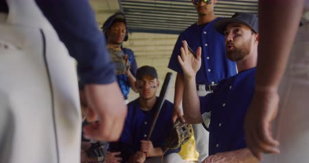 guantone : Low angle side view of a Caucasian male baseball coach, giving instructions to a team of multi-ethnic male baseball players gathered around him, preparing in the changing room before a game, in slow motion