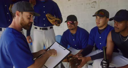 amontoado : Side view close up of a Caucasian male baseball coach explaining a game plan and instructing a multi-ethnic team of male baseball players, preparing before a game, sitting in a changing room, in slow motion Stock Footage