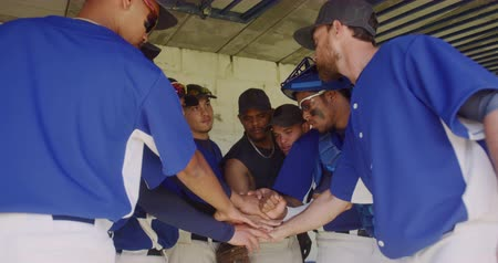 amontoado : Side view of a multi-ethnic group of male baseball players, preparing for a game, standing in a changing room, motivating each other and stacking hands, in slow motion