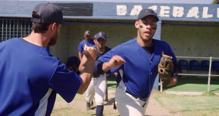 holding onto : Front view of a multi-ethnic group of male baseball players, running onto the pitch before a game and fist bumping with their coach on a sunny day, in slow motion