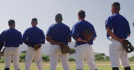 v řadě : Rear view of a multi-ethnic team of male baseball players, preparing before a game, standing in a row, holding their caps on their chests, listening to national anthem on a sunny day in slow motion