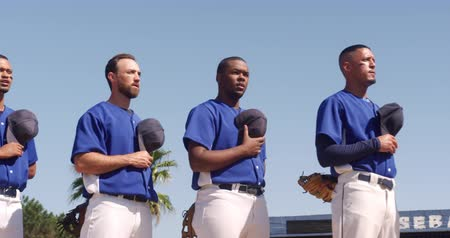 marş : Front view close up of a multi-ethnic team of male baseball players, preparing before a game, standing in a row, holding their caps on their chests, listening to national anthem and singing on a sunny day, in slow motion