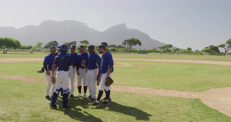 amontoado : Side view of multi-ethnic team of male baseball players preparing before a game, in a huddle on a baseball field, listening to their captain giving them instructions, on a sunny day, in slow motion