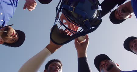 stapelen : Low angle view of a multi-ethnic team of male baseball players, preparing before a game, linking hands by grabbing a baseball helmet, holding a baseball on a sunny day, in slow motion Stockvideo