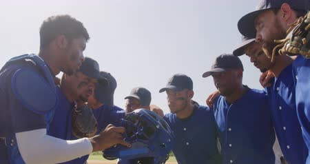 amontoado : Side view of multi-ethnic group of male baseball players, preparing before a game, huddling on a baseball field,listening to their captain giving them instructions on a sunny day in slow motion