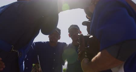 capitão : Side view of multi-ethnic team of male baseball players, preparing before a game, in a huddle on a baseball field, listening to their captain giving them instructions, backlit on a sunny day, in slow motion