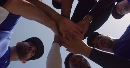 stapelen : Low angle view of a multi-ethnic team of male baseball players, preparing before a game, motivating each other in a huddle making a hand stack on a sunny day, in slow motion