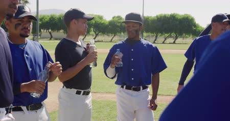 beisebol : Side view of a team of multi-ethnic male baseball players, preparing before a game, resting, drinking water and talking on a sunny day, in slow motion