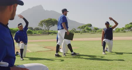 beisebol : Side view of a Caucasian male baseball coach instructing a multi-ethnic team of male baseball players during a training session on a playing field on a sunny day, preparing before a game, kneeling down and stretching, doing exercises, in slow motion Stock Footage