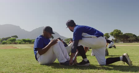 undefined : Side view of a Caucasian male baseball coach instructing a multi-ethnic group of male baseball players, training before a game, working out doing sit ups at a playing field on a sunny day, in slow motion