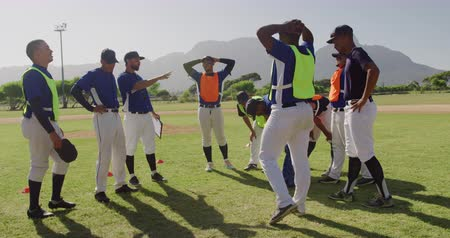 beisebol : Side view of a multi-ethnic group of male baseball players and their coach, resting and talking during a training session at a playing field on a sunny day in slow motion