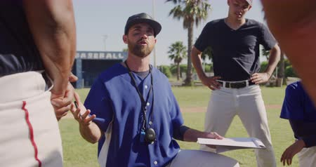 amontoado : Front view of a Caucasian male baseball trainer holding a clipboard and instructing a multi-ethnic team of male baseball players, preparing them before a game at a playing field on a sunny day, backlit, in slow motion