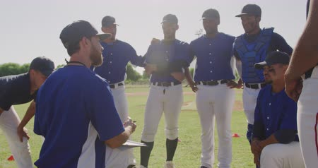 amontoado : Side view of a Caucasian male baseball trainer instructing a multi-ethnic team of male baseball players, preparing them before a game at a playing field, backlit, in slow motion