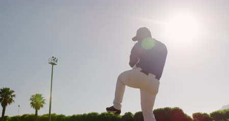 jarro : Low angle side view of a mixed race male baseball player, pitching a ball during a baseball game, on a sunny day, backlit, in slow motion