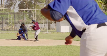 vleermuis : Rear view close up of a mixed race male baseball player during a baseball game, pitching a ball, with a hitter failing to hit it and the catcher cathing it in the background on a sunny day, in slow motion Stockvideo