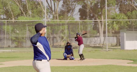 jarro : Rear view of a mixed race male baseball player during a baseball game, pitching a ball, with a hitter failing to hit it and the catcher cathing it in the background on a sunny day, in slow motion Vídeos
