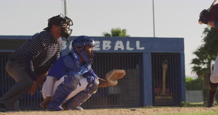 vleermuis : Side view of a mixed race male baseball player, during a baseball game, squatting and catching a ball on a sunny day in slow motion Stockvideo
