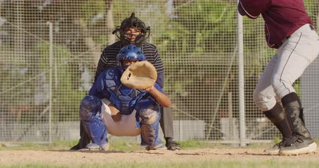 vleermuis : Front view of a mixed race male baseball player during a baseball game on a sunny day, playing in the catcher position, squatting and catching a ball missed by the hitter, in slow motion
