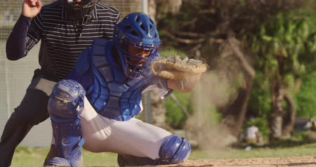 guantone : Front view of a mixed race male baseball player during a baseball game on a sunny day, playing in the catcher position, squatting and catching a ball, in slow motion