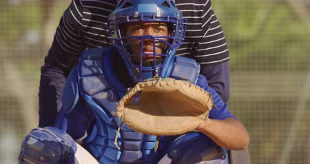 guantone : Front view close up of a mixed race male baseball player, playing in the catcher position during a baseball game on a sunny day, squatting and catching a ball, in slow motion