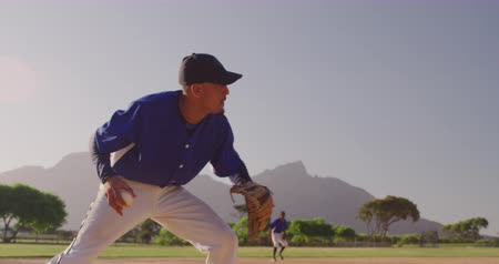 házení : Side view of a mixed race male baseball player during a baseball game on a sunny day, catching a ball in his mitt and throwing it, with his teammates in the background, in slow motion