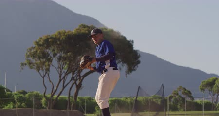 guantone : Front view of a mixed race male baseball player, during a baseball game on a sunny day, catching a high flying ball in his mitt and throwing it, in slow motion