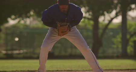 beisebol : Front view of a mixed race male baseball player during a baseball game on a sunny day, catching a low ball in his mitt and throwing it, in slow motion Stock Footage
