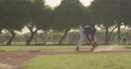 guantone : Front view of a mixed race male baseball player during a baseball game on a sunny day, catching a low ball in his mitt and throwing it, in slow motion Filmati Stock