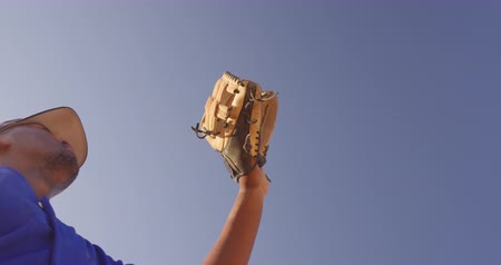 guantone : Low angle close up of a mixed race male baseball player during a baseball game, holding up his mitt against the blue sky and catching a ball in it, in slow motion Filmati Stock