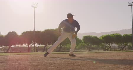 beisebol : Front view of a mixed race male baseball player during a baseball game on a sunny day, catching a ball in his mitt and throwing it, with anoter player in the background, backlit, in slow motion